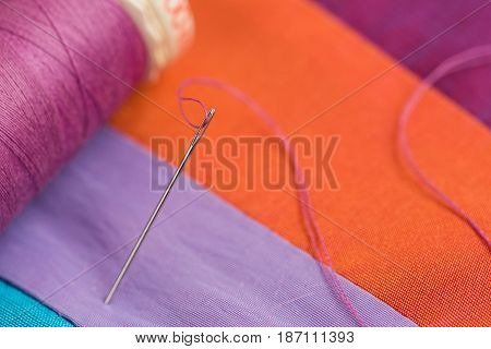quilting, sewing, tailoring and fashion concept - macro of spool of threads, needle, beautiful colored patchwork fabrics, colorful stitched textile scraps at workshop, top view