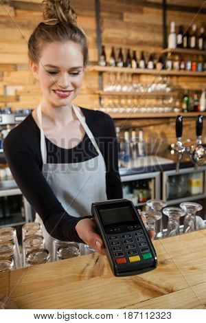Smiling woman holding credit card reader at cafe shop