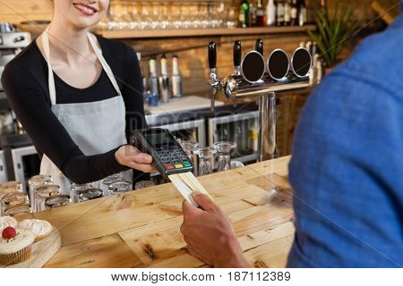 Man making payment on credit card reader machine at cafe shop