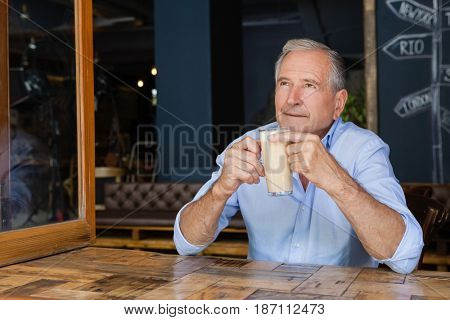 Senior thoughtful man holding cold coffee while sitting in cafe shop