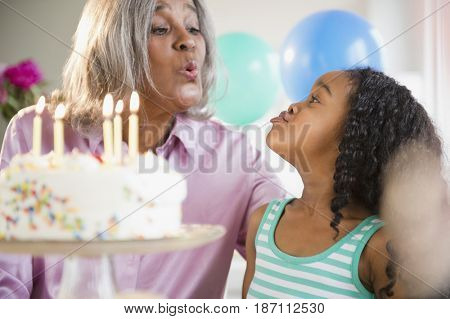 African American grandmother and granddaughter with birthday cake