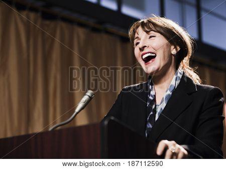 Caucasian businesswoman speaking at podium