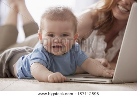 Caucasian mother and son using laptop on floor