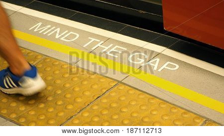 Mind the gap text sign on floor between train and platform station and high angle view.