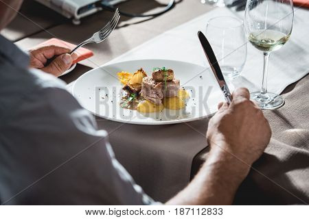 man is preparing to eat delicious roulade of rabbit meat in a restaurant. small portion.