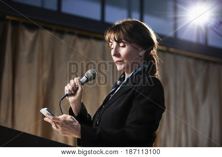 Caucasian businesswoman speaking into microphone and using cell phone
