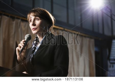 Caucasian businesswoman speaking into microphone