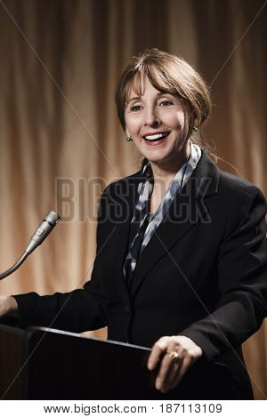 Caucasian businesswoman speaking at podium