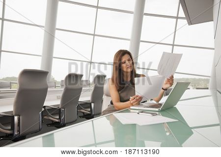 Caucasian businesswoman working in conference room