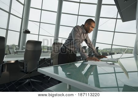 Black businessman using laptop in conference room