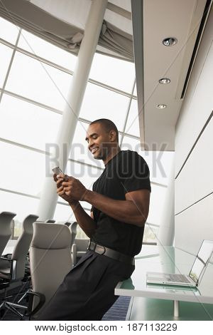 Black businessman using cell phone in conference room
