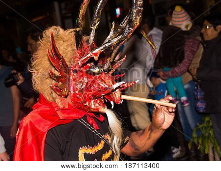 Quito, Ecuador - february 02, 2016: An unidentified man dressed up participating in the Diablada, with a demon mask in his head with a stick in his hand.