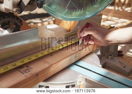 Mixed race man measuring wood on saw