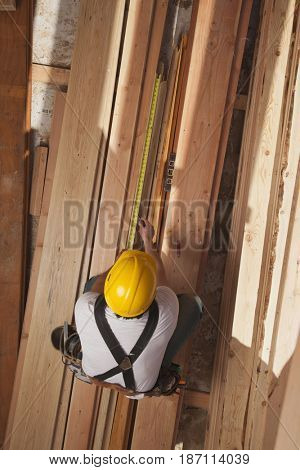 Mixed race construction worker measuring lumber
