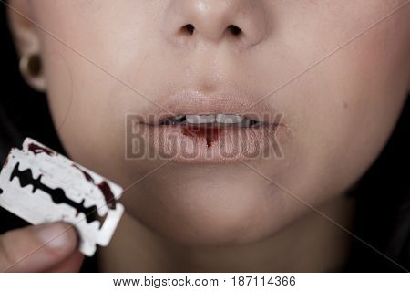 Quito, Ecuador - May 09, 2017: Close up of an anxious teenager in day 14 blue whale challenge cutting her lips with a gillette, social suicide concept as a sociology metaphor for crowd or herd mentality and group decisions resulting in violence or populat