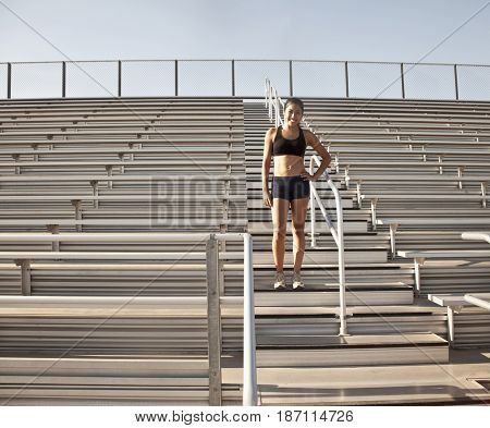 Mixed race runner standing in bleachers