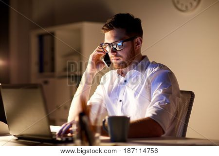 business, overwork, people, deadline and technology concept - businessman in glasses with laptop computer calling on smartphone at night office