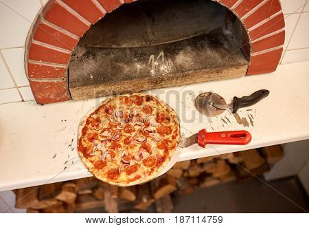 food, italian kitchen, culinary and cooking concept - baked pizza on peel and cutter at pizzeria oven