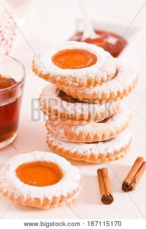 Teatime biscuits with cinnamon tea on white dish.
