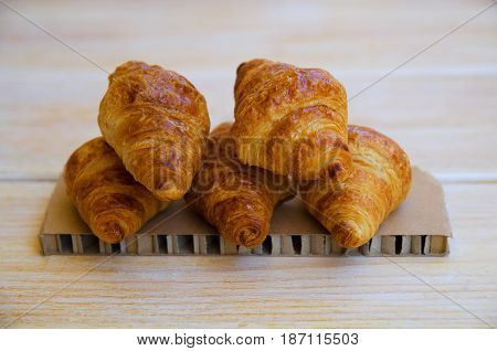Group of tasty buttery croissants on wooden table. French pastry for breakfast.