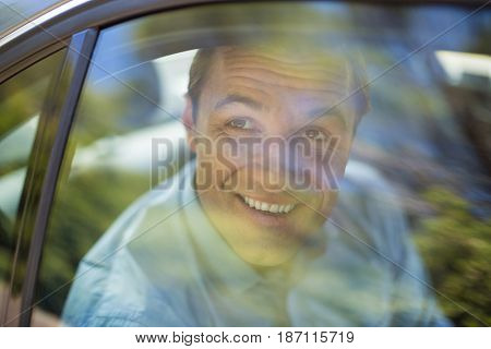 Smiling man looking through car window