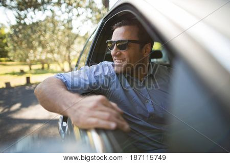 Smiling young man sitting in car