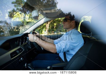 Side view of young man driving car