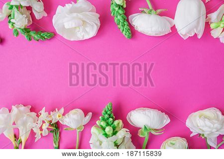 Floral frame made of white ranunculus, snapdragon, tulip and freesia flowers on pink background. Flat lay, top view. Pattern of flowers.