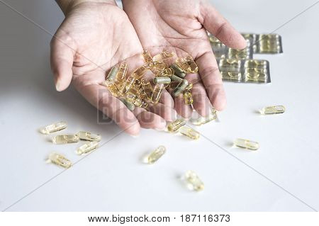 Holding yellow Capsule pills in both hands