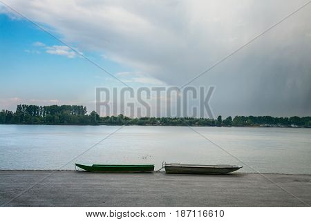 Two fishing boats on Zemun Quay (Zemunski kej) in a cloudy afternoon over the Danube river Belgrade capital city of Serbia