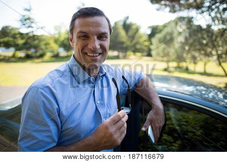 Portrait of smiling young man holding mobile phone and sunglasses by car