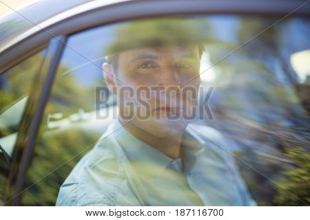 Serious man seen through car window