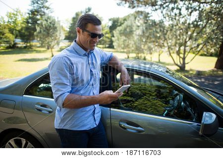 Smiling young man holding mobile phone by car