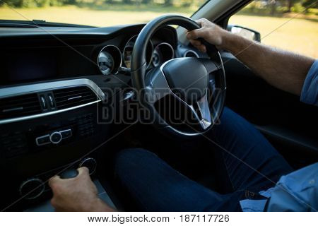 Mid section of man driving car