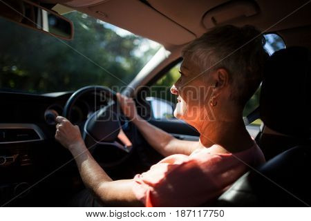 Senior woman driving car on sunny day