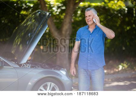 Confused senior man talking on phone by breakdown car