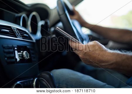 Mid section of man using mobile phone while driving car