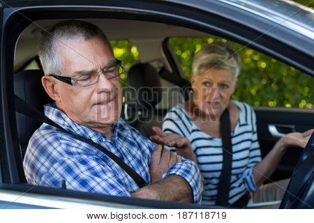 Annoyed senior man with woman sitting in car