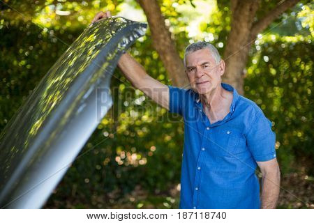 Portrait of tensed senior man opening car hood