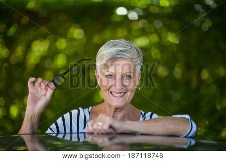 Portrait of senior woman holding eyeglasses while leaning on car roof
