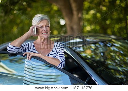 Annoyed senior woman talking on phone by car