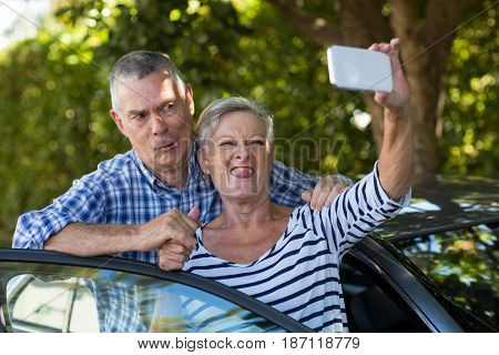 Playful senior couple taking selfie by car