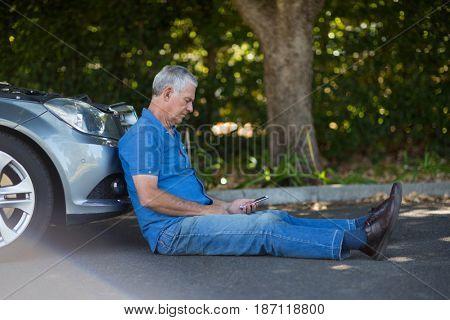 Senior man sitting by car on road after breakdown