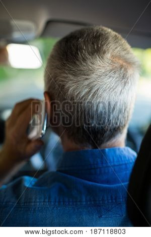 Rear view of senior man talking on phone while driving car