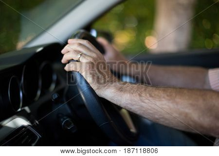 Cropped hands of senior man driving car