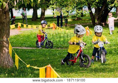 Russia. Moscow. Vorontsovsky Park on the 21st of August. STRIDER CUB 2016. Children go to the balancebike along the path in the park