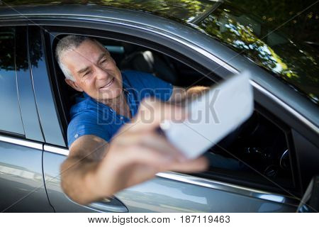 Smiling senior man taking selfie while sitting in car