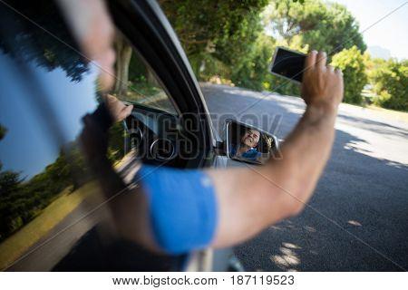 Senior man taking selfie while driving car on road