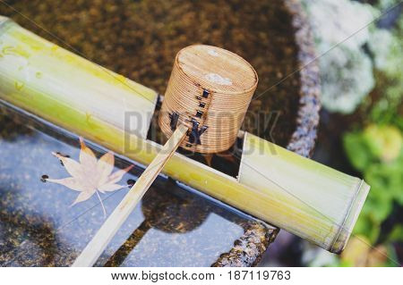 Japanese wooden purification dipper in a chozubachi or water basin used to rinse the hands in Japanese temples shrines and gardens. poster