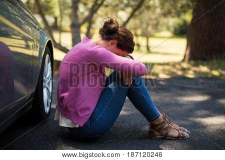 Sad woman sitting by breakdown car